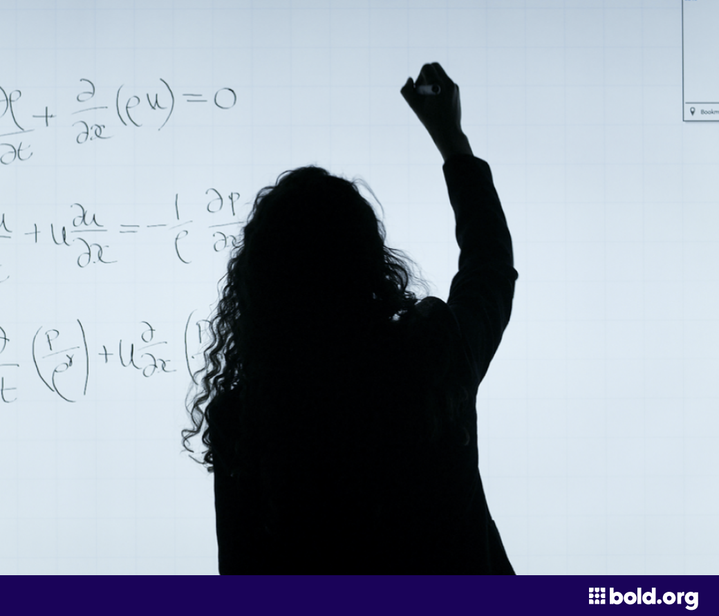 Woman completing an equation on a white board