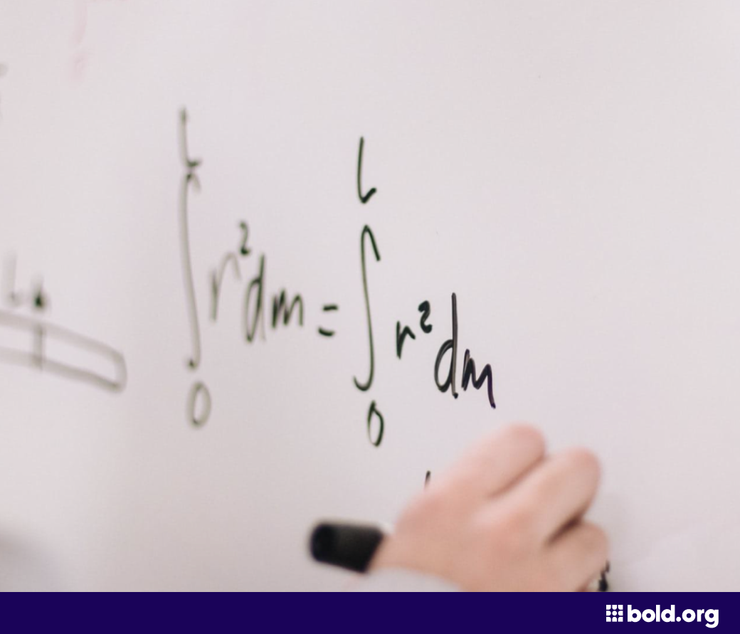 Person writing an equation on a whiteboard