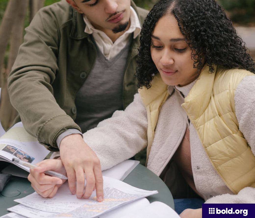 Two students looking at notes and textbooks on a table outside.